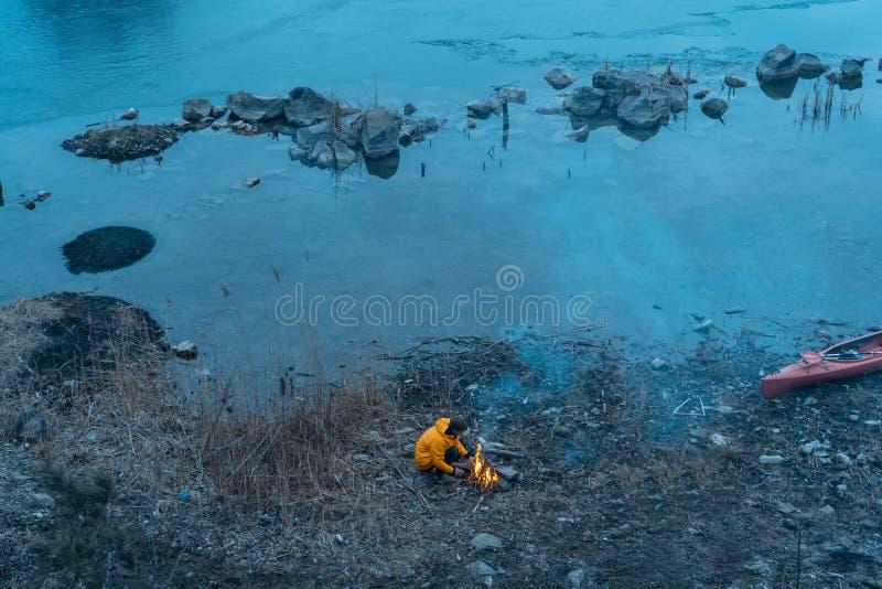 Le type sur le lac fait un feu photographie stock libre de droits