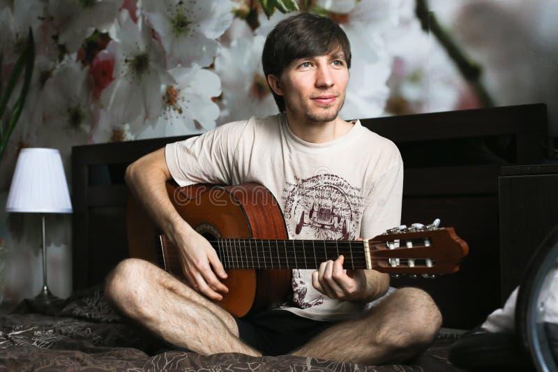 Le type sur le lit jouant la guitare classique images libres de droits