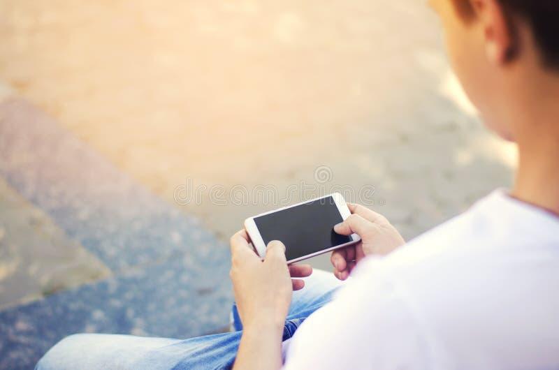 Le type tient un smartphone mobile et regarde l'écran la dépendance de téléphone, réseaux sociaux Travail sur l'Internet Wri photographie stock libre de droits