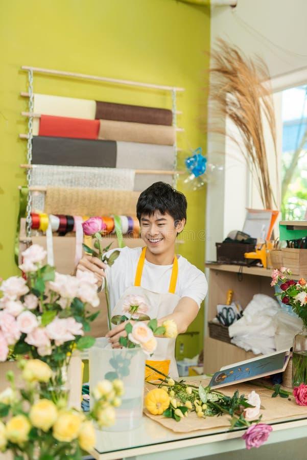 Le ung asiatisk blomsterhandlaremandanande samla ihop på blomsterhandeln arkivbild