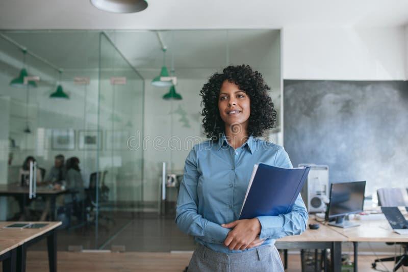 Le unga affärskvinnainnehavmappar, medan stå i ett kontor arkivbild