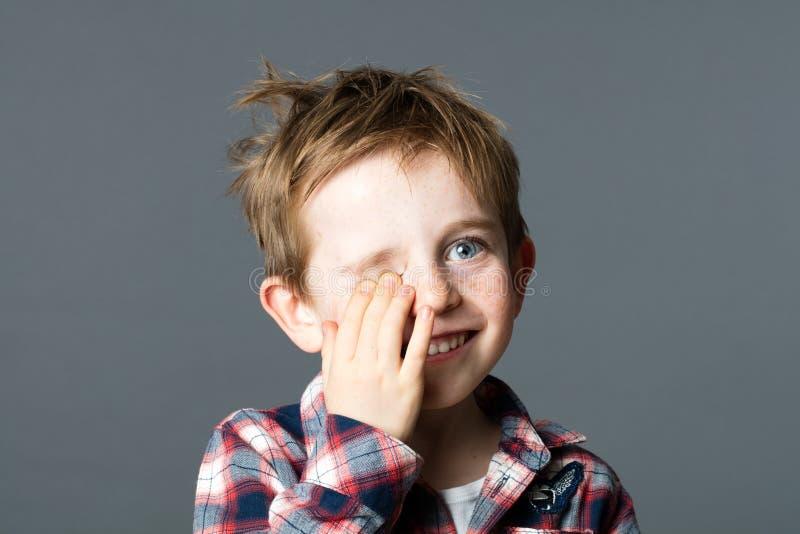 Le unga barnet som döljer ett öga för glad kurragömma arkivfoto