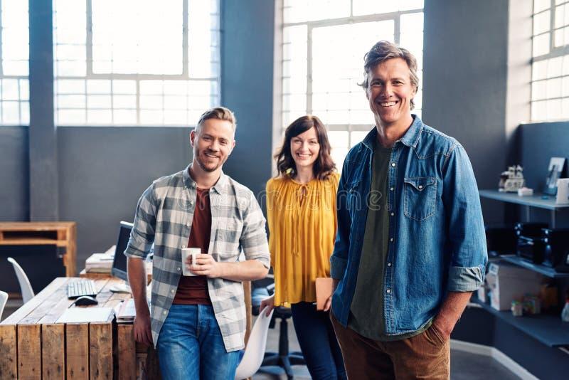 Le unga coworkers som tillsammans står i ett modernt kontor arkivbilder