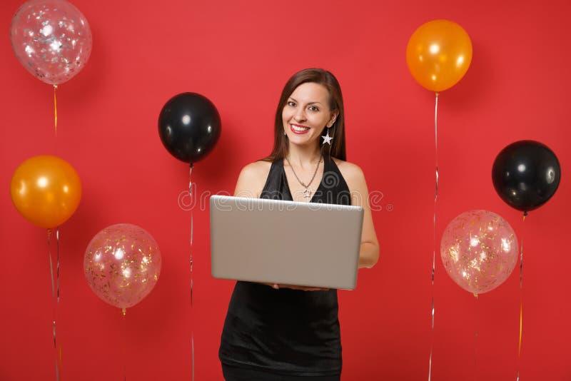 Le unga flickan i den lilla svarta klänningen som arbetar på bärbar datorPCdatoren, medan fira på röda bakgrundsluftballonger arkivbild