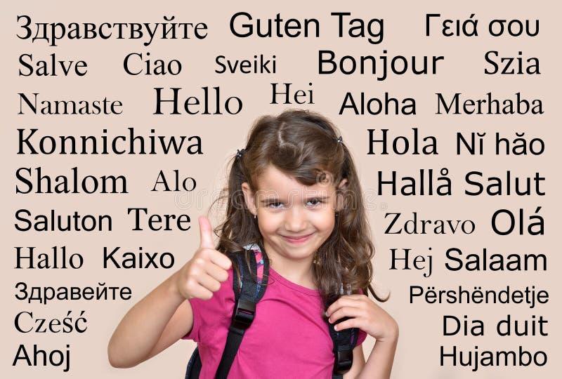 Le unga flickan med hälsninghälsning i många olika språk arkivfoto