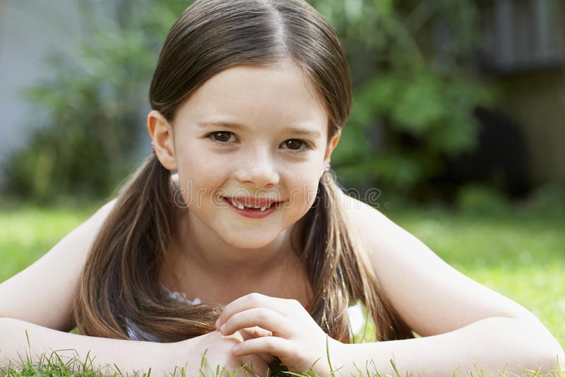 Le unga flickan som ligger i gräs arkivfoto