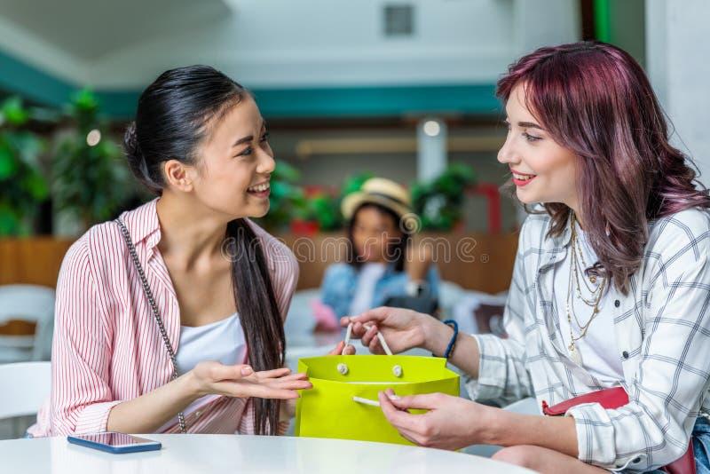 Le unga kvinnor med shoppingpåsen som tillsammans sitter och samtal fotografering för bildbyråer