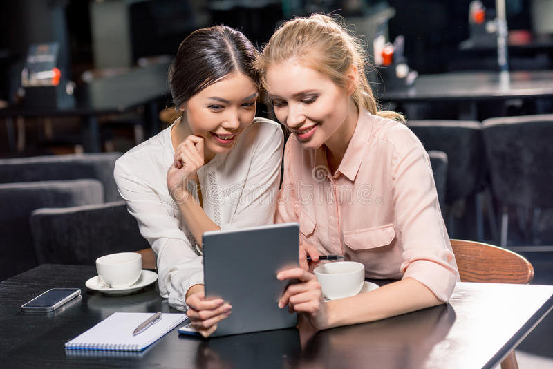 Le unga kvinnor som använder den digitala minnestavlan, medan dricka kaffe i kafé arkivbilder