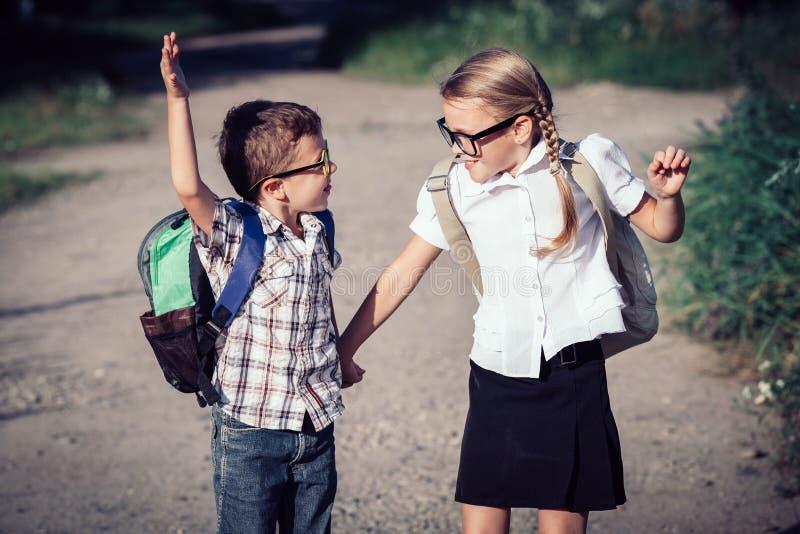 Le unga skolbarn i en banhoppning för skolalikformig på arkivfoton