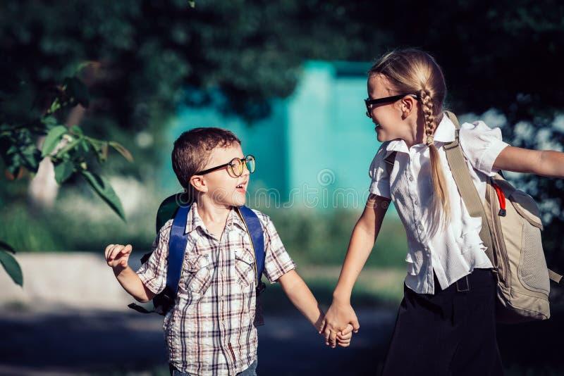 Le unga skolbarn i en banhoppning för skolalikformig på royaltyfri bild