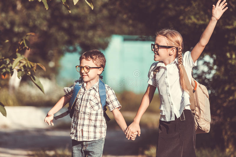Le unga skolbarn i en skolalikformig mot ett träd arkivbilder