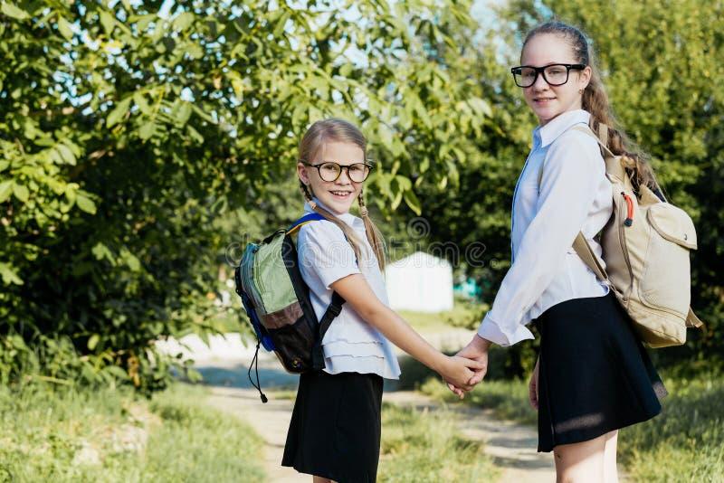 Le unga skolbarn i en skolalikformig som igen står arkivbild