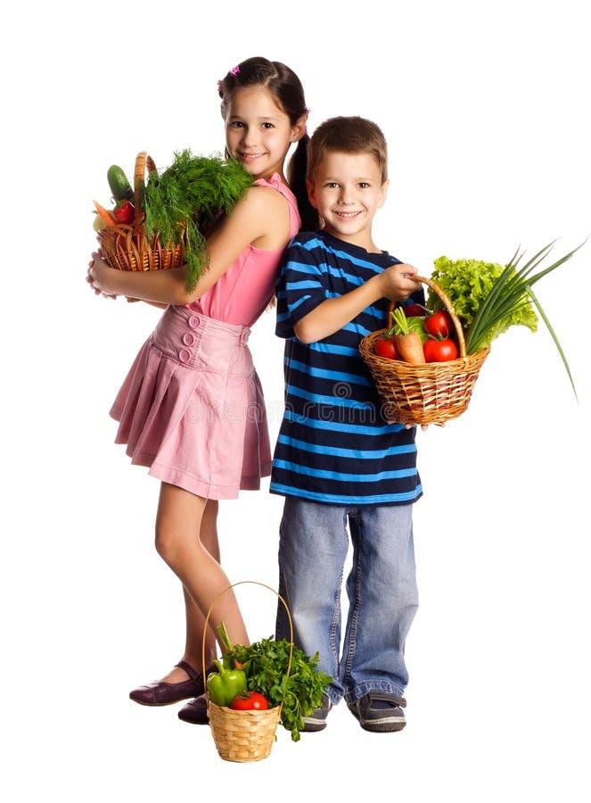 Le ungar med grönsaker i korg arkivbild
