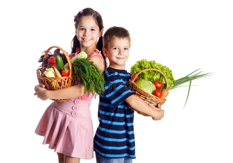 Le ungar med grönsaker i korg royaltyfria bilder