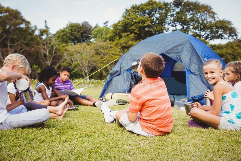 Le ungar som tillsammans ligger på gräset royaltyfri bild