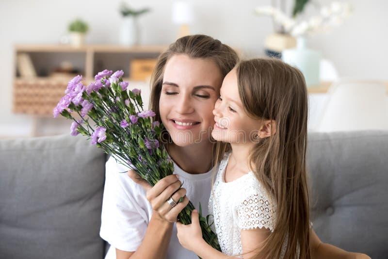Le ungedottern som ger blommor som gratulerar mamman med malen royaltyfria foton