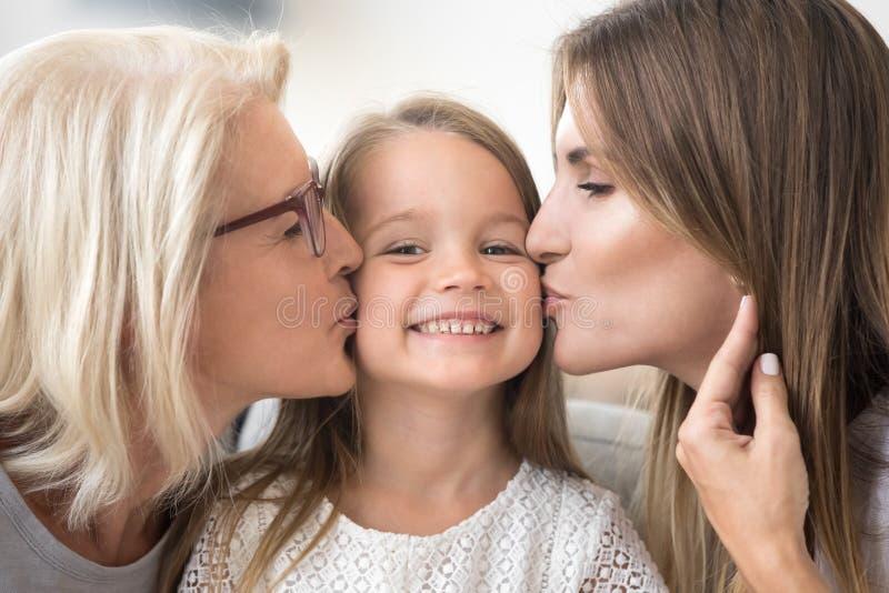 Le ungeflickan tycker om mamman och mormodern som kysser på kinder arkivbilder