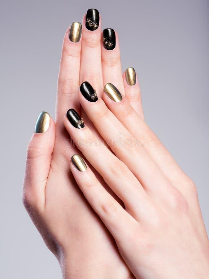 Le unghie della bella donna con il manicure creativo fotografia stock