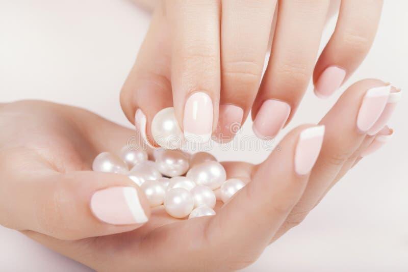 Le unghie della bella donna con il manicure francese fotografia stock libera da diritti