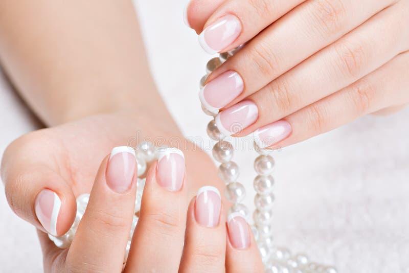 Le unghie della bella donna con il manicure francese e le perle immagini stock