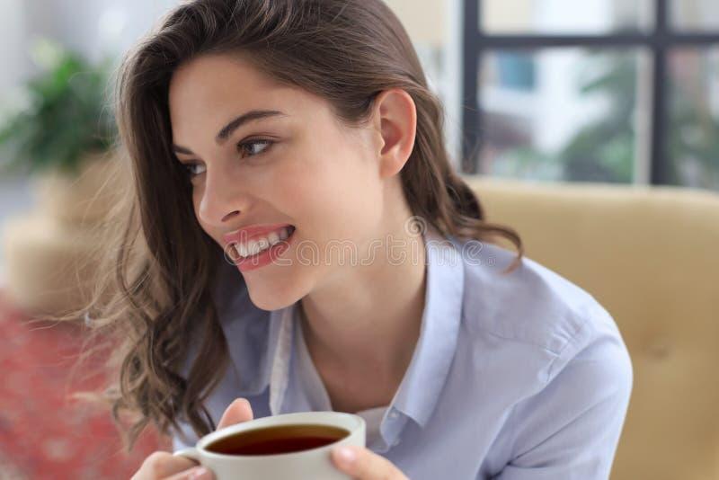 Le ungt kvinnligt sammanträde i fåtöljen i vardagsrummet som rymmer en kopp kaffe fotografering för bildbyråer