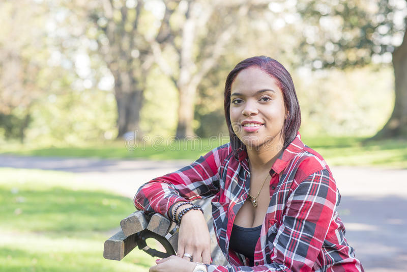 Le ungt latinskt kvinnasammanträde på bänk i parkera royaltyfri fotografi