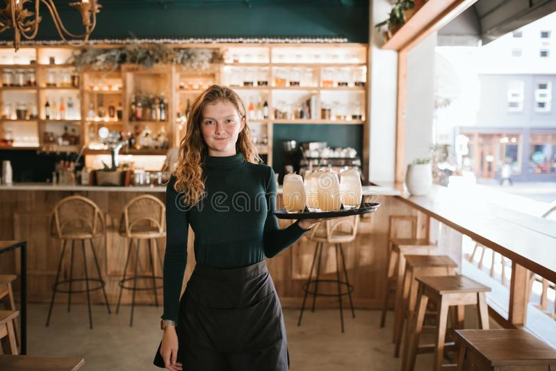 Le ungt servitrisanseende med ett magasin av drinkar royaltyfri foto