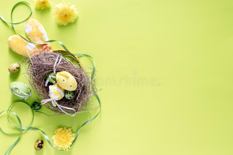 Le uova di Pasqua Colourful in uccelli annidano con la decorazione festiva sul fondo luminoso di verde di calce, immagine di vist fotografia stock libera da diritti