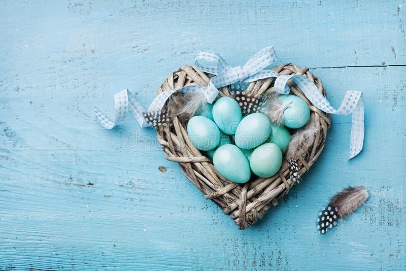 Le uova di Pasqua dipinte nel cuore annidano sulla vista superiore del fondo d'annata del turchese nello stile di disposizione de fotografia stock