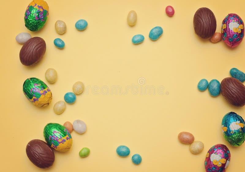 Le uova di Pasqua gradiscono un fondo Uova di Pasqua del cioccolato, dolci su fondo di legno fotografia stock