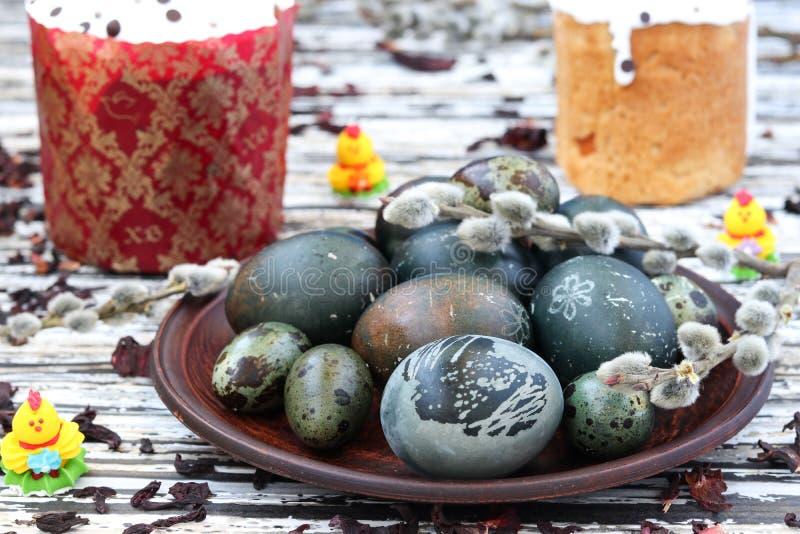 Le uova di Pasqua hanno dipinto il tè del karkade, i dolci su un piatto, natura morta di Pasqua immagine stock