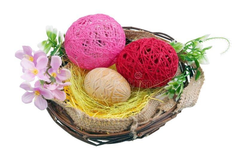 Le uova di Pasqua hanno fatto di legno e del filo in un nido dei ramoscelli della betulla isolati fotografia stock