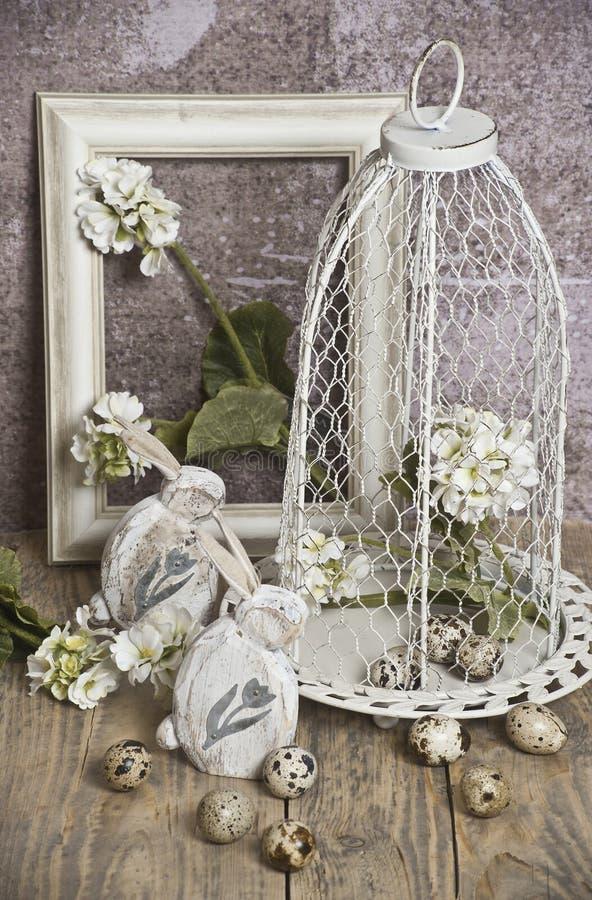 Le uova di Pasqua in una gabbia, balzano fiori bianchi, le uova di quaglia, coniglietti bianchi fotografia stock