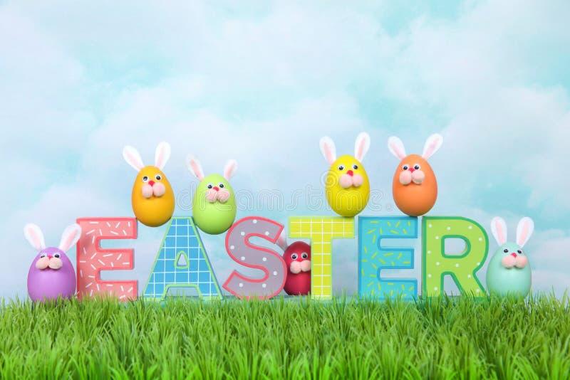 Le uova divertenti del coniglietto di pasqua dei fronti su PASQUA di legno firmano dentro l'erba fotografie stock libere da diritti