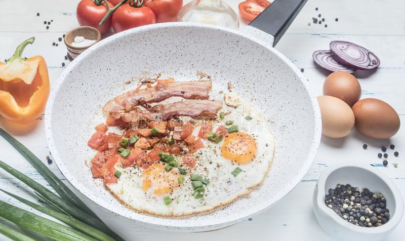 Le uova rimescolate casalinghe con bacon, i pomodori, le cipolle verdi, il peperone dolce ed i condimenti sulla padella bianca, i immagine stock libera da diritti