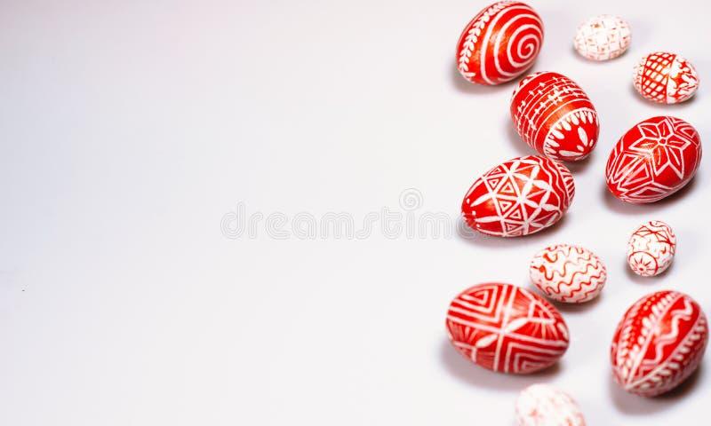 Le uova rosse di Pasqua con il modello bianco piega hanno sparso il fondo bianco dalla destra Uova tradizionali ucraine immagini stock