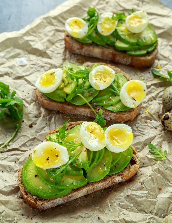Le uova sane di quaglia e dell'avocado tosta con il razzo ed il sale marino selvaggi immagini stock libere da diritti