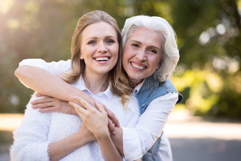 Le vänlig kvinna som två kramar i parkera royaltyfri bild