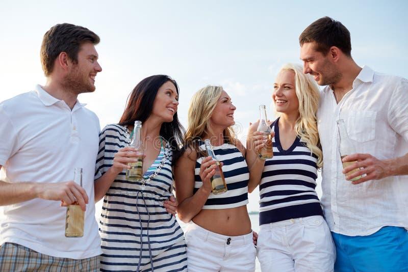 Le vänner med drinkar i flaskor på stranden arkivbilder