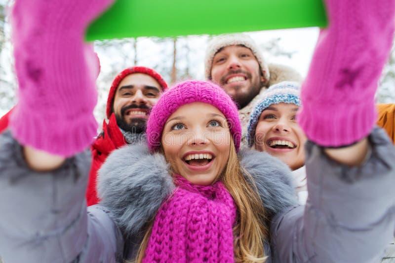 Le vänner med minnestavlaPC i vinterskog royaltyfria bilder