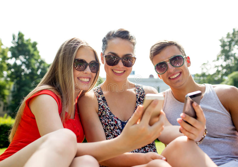 Le vänner med smartphonedanandeselfie arkivfoton