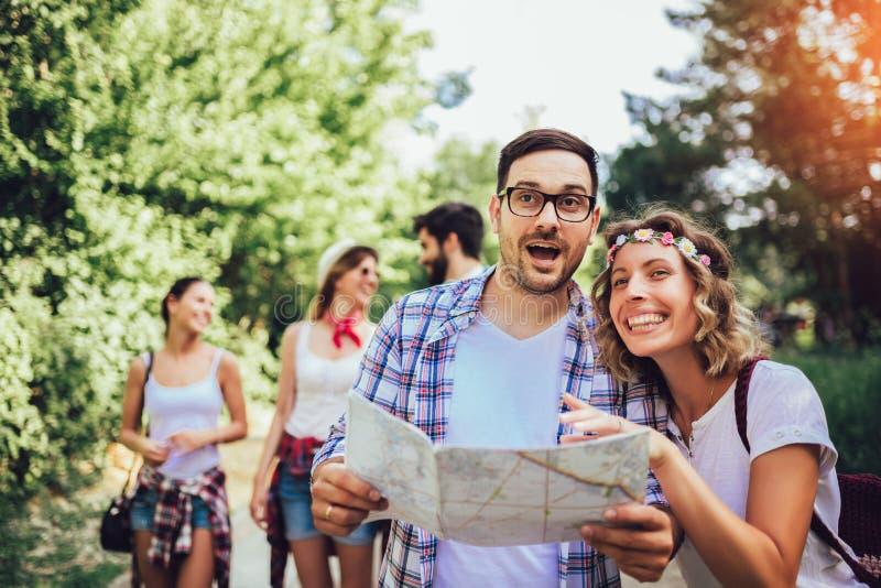 Le vänner som går med ryggsäckar i trän - affärsföretag, lopp, turism, vandring och folkbegrepp arkivbilder