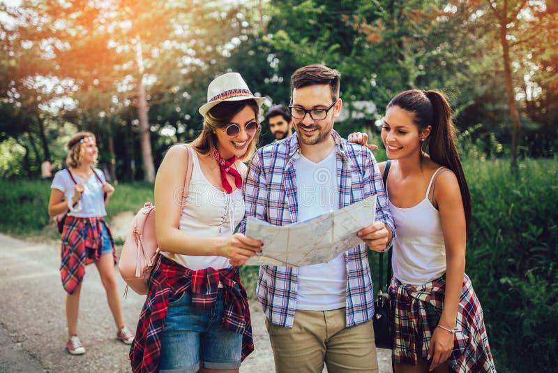 Le vänner som går med ryggsäckar i trän - affärsföretag, lopp, turism, vandring och folkbegrepp royaltyfria foton
