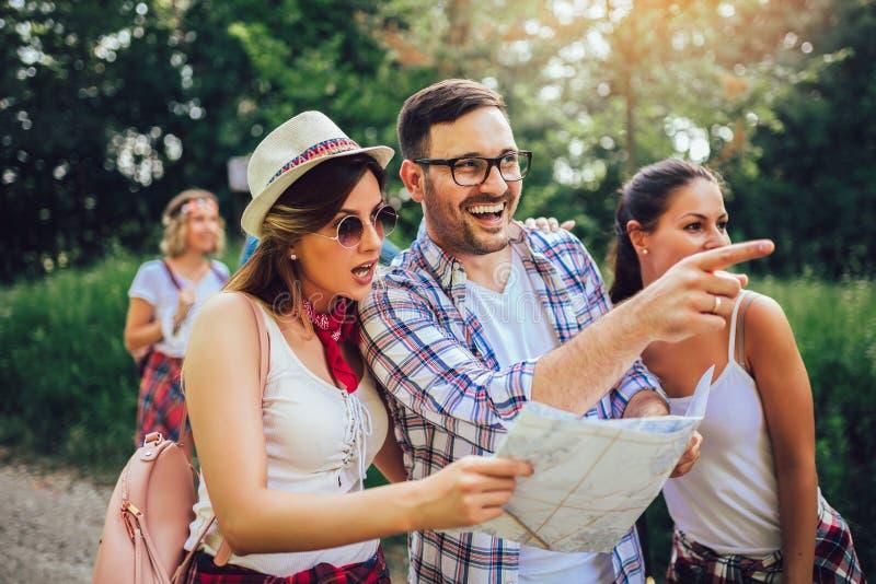 Le vänner som går med ryggsäckar i trän - affärsföretag, lopp, turism, vandring och folkbegrepp royaltyfri foto