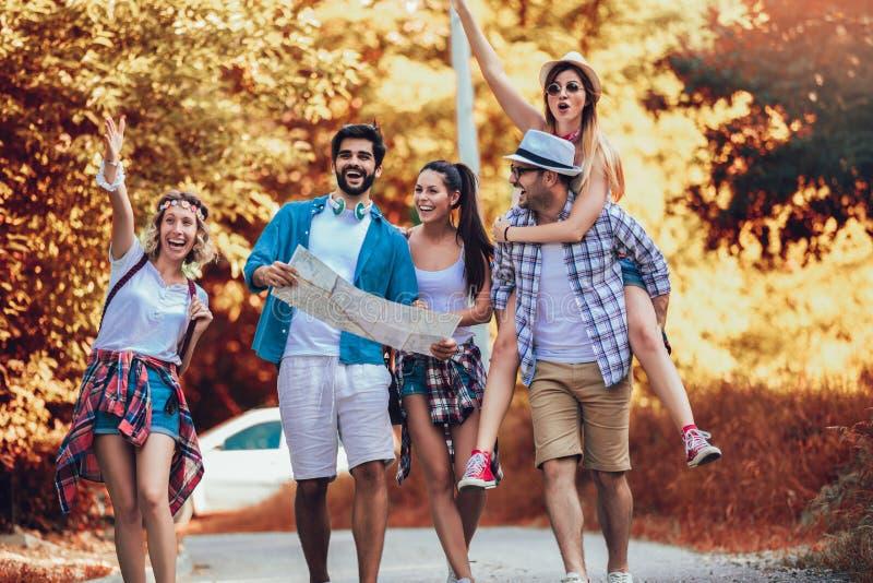 Le vänner som går med ryggsäckar i trän - affärsföretag, lopp, turism, vandring och folkbegrepp arkivbild