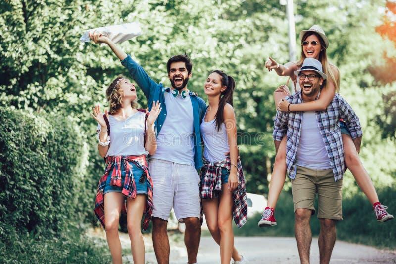 Le vänner som går med ryggsäckar i trän - affärsföretag, lopp, turism, vandring och folkbegrepp royaltyfri fotografi