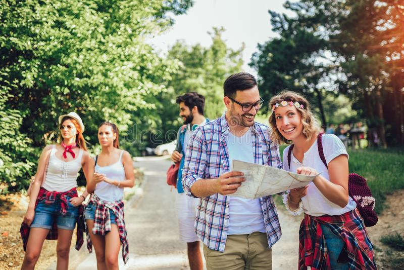 Le vänner som går med ryggsäckar i trän - affärsföretag, lopp, turism, vandring och folkbegrepp arkivfoto
