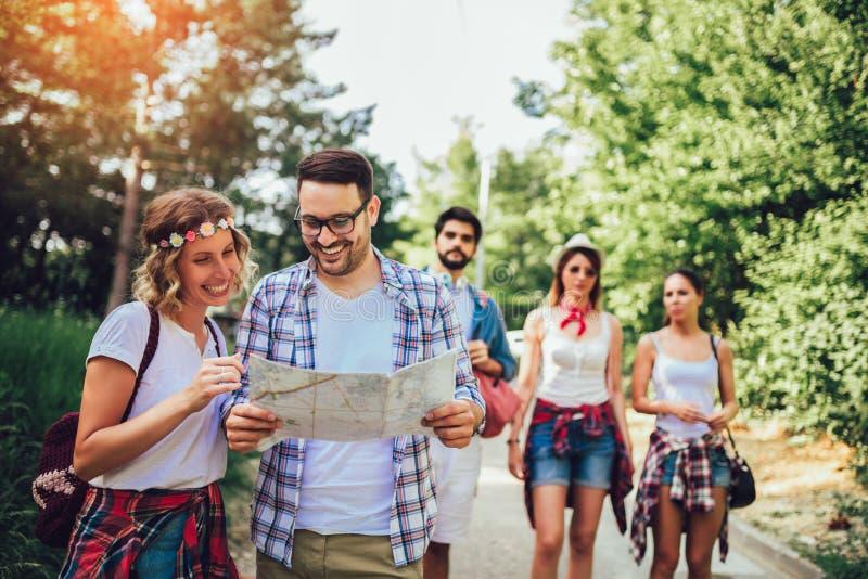 Le vänner som går med ryggsäckar i trän - affärsföretag, lopp, turism, vandring och folkbegrepp fotografering för bildbyråer