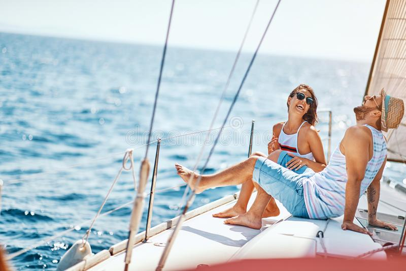 Le vänner som kopplar av på en lyxig yacht Par p? kryssning arkivfoto