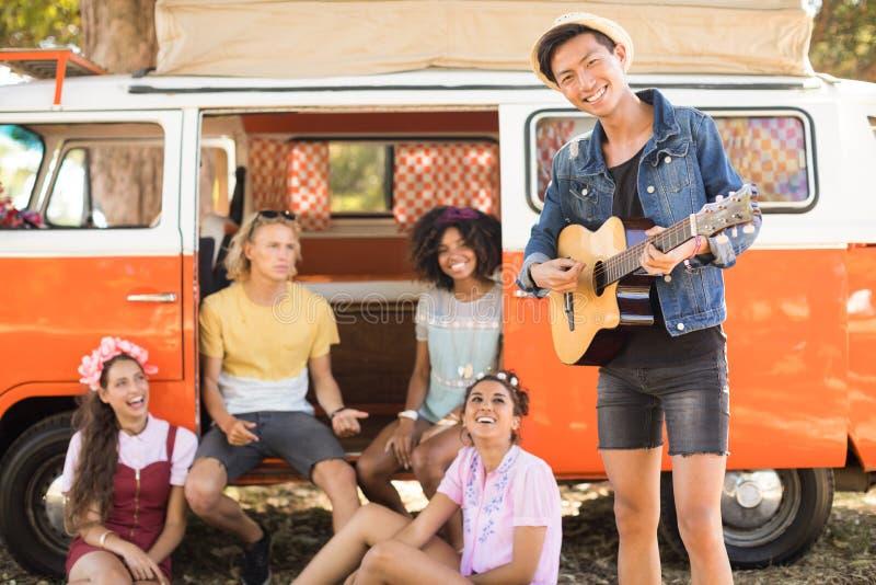 Le vänner som ser mannen som spelar gitarren royaltyfri foto